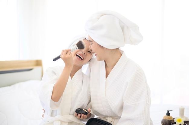 Uma linda mãe e filha feliz em um roupão de banho branco aplicando maquiagem natural