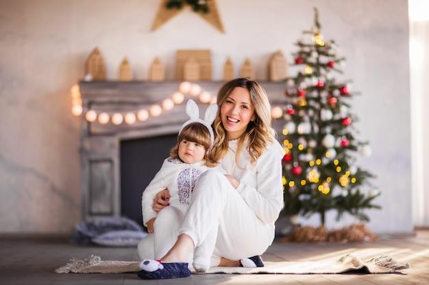 Uma linda mãe loira e uma criança em trajes de coelhinhos fofos brancos estão rindo no contexto de uma árvore de natal e uma lareira. foto de alta qualidade