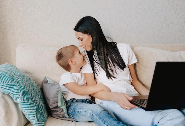 Uma linda mãe sentada com um laptop nas mãos ao lado de seu filho pequeno no sofá de casa olhando um para o outro