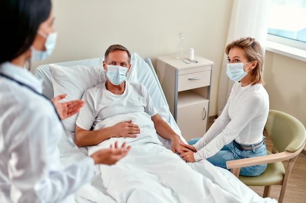 Uma linda médica com uma máscara médica protetora se comunica com a família de um paciente maduro que está deitado em uma enfermaria de hospital moderno durante o coronavírus ou epidemia de covid-19.