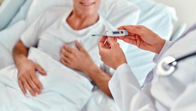 Uma linda médica mede a temperatura de um paciente adulto do sexo masculino que está passando por reabilitação em uma enfermaria de hospital moderno.