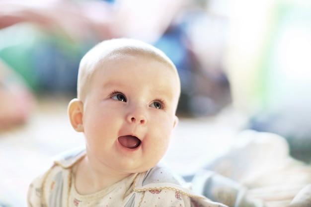 Uma linda menina com asas de fada ri enquanto olha para a câmera.
