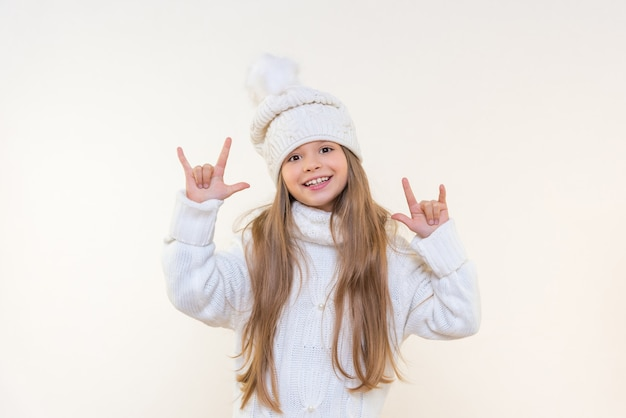 Uma linda menina com um chapéu e um suéter de inverno sobre um fundo branco e isolado fica muito feliz e aponta os dedos para o lado