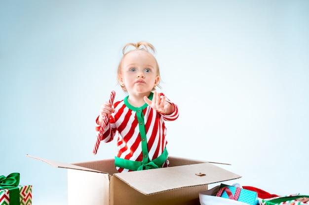 Uma linda menina de 1 ano sentada em uma caixa no natal