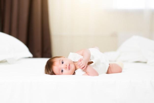 Uma linda menina de 3 meses em casa com roupa de cama branca fica bem para a câmera