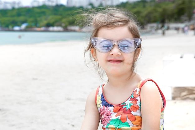 Uma linda menina de óculos na praia à beira-mar. entretenimento e recreação de verão.
