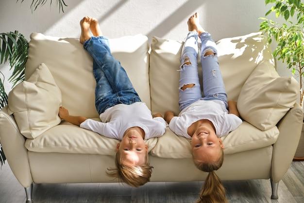 Uma linda menina e um menino estão deitados de costas no sofá da sala de estar, olhando para a câmera e sorrindo enquanto brincam em casa
