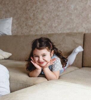 Uma linda menina encontra-se no sofá com as mãos sob a cabeça e sorri. retrato grande