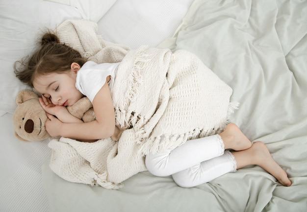 Uma linda menina está dormindo em uma cama com um ursinho de pelúcia. conceito de desenvolvimento infantil e sono. a vista do topo.