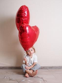 Uma linda menina está sentada em casa no chão com bolas vermelhas em forma de coração nas mãos. dia dos namorados.