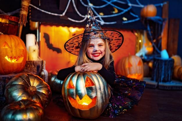 Uma linda menina fantasiada de bruxa comemora em casa em um interior com abóboras e casa mágica de papelão ao fundo