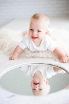 Uma linda menina feliz de 7 meses na fralda deitada e brincando