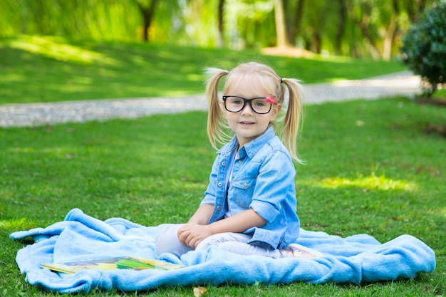 Uma linda menina loira com cabelos loiros e óculos de leitura, lendo um livro em um parque