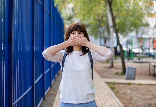 Uma linda menina morena cobriu a boca com as mãos. não diga nada. gesto de silêncio. uma garota em uma jaqueta branca está de pé na rua.