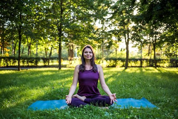 Uma linda menina morena com um agasalho senta-se em um tapete de ioga azul e olha para a câmera contra o pôr do sol em uma clareira