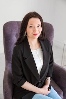 Uma linda menina morena com uma jaqueta preta e uma camiseta leve se senta em uma cadeira, sorri e olha para a câmera.