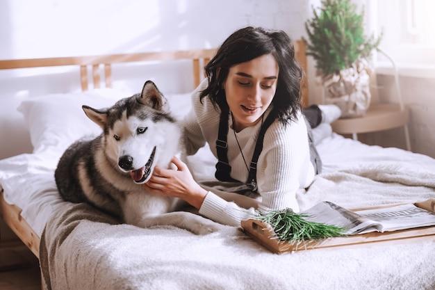 Uma linda menina morena deita-se na cama com um cachorro husky branco em casa. manhã ensolarada