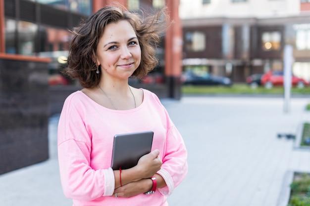 Uma linda menina morena em roupas da moda é de pé e segurando um tablet ao ar livre no verão.
