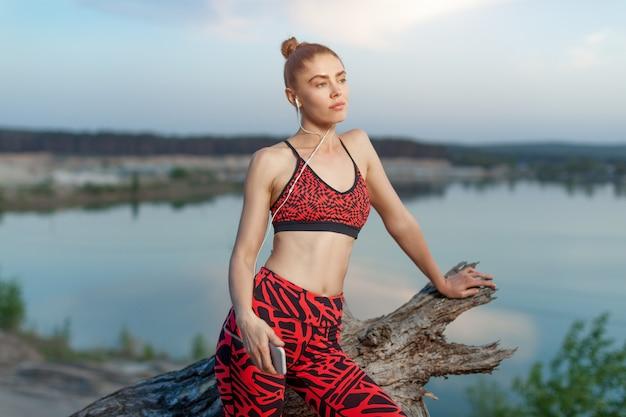 Uma linda menina morena em roupas esportivas elegantes está descansando depois de um treino ativo esporte perto do lago.
