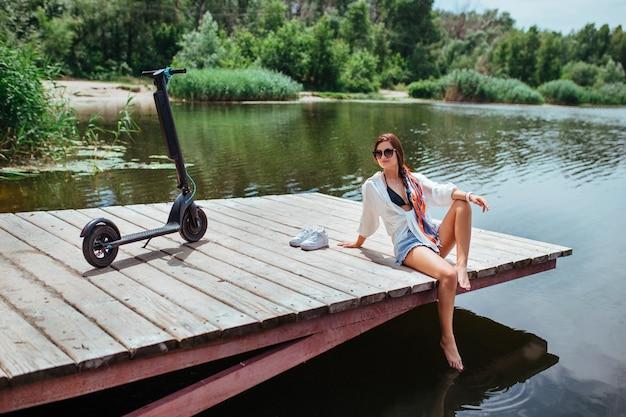 Uma linda menina morena repousa sobre uma ponte de madeira perto do rio, ao lado de uma scooter elétrica. o conceito de ecologia e transporte elétrico.