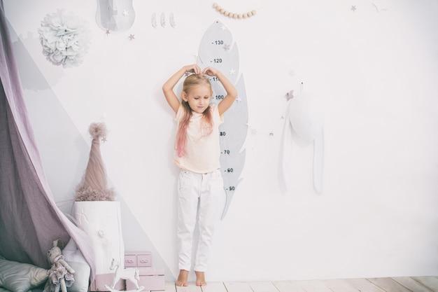 Uma linda menina na sala de jogos infantil mede sua altura