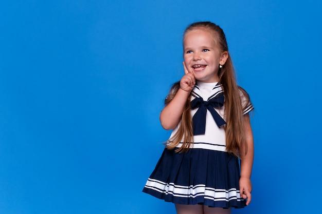 Uma linda menina sorridente e adorável aponta o dedo para o lado