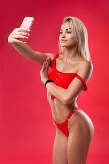 Uma linda modelo de maiô faz uma selfie em um fundo vermelho com o novo iphone