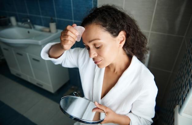 Uma linda morena com um roupão de waffle branco cuida do rosto, faz uma massagem facial de drenagem linfática e olha seu reflexo em um pequeno espelho de maquilhagem