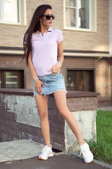 Uma linda morena de camiseta e saia jeans alisa o cabelo em uma rua da cidade.