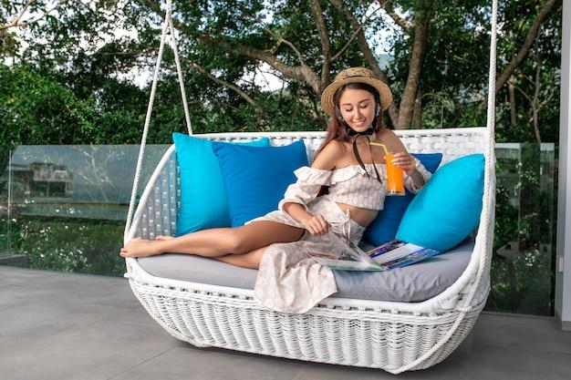 Uma linda morena de chapéu se senta em um sofá com um coquetel de laranja na mão e seleciona bebidas tropicais ou comida no menu.