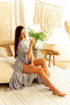 Uma linda morena está curtindo o tempo sozinha. ela está bebendo café e vestindo um robe. conceito de vida de movimento lento