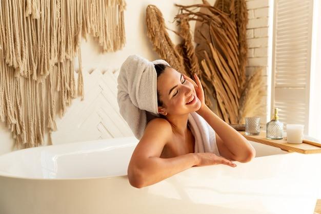 Uma linda morena está curtindo o tempo sozinha. ela toma banho e toca o rosto. tem uma toalha na cabeça dela e ela ri