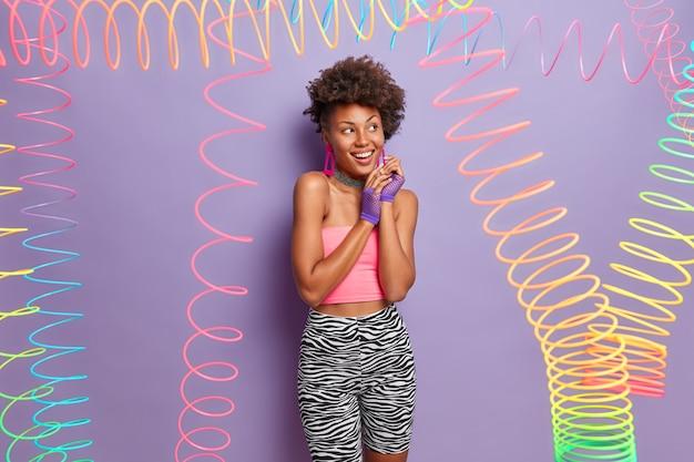 Uma linda mulher afro-americana mantém as mãos juntas, olha de lado, sorri amplamente, vestida com roupas esportivas casuais