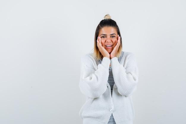 Uma linda mulher ajeitando o rosto nas mãos com uma camiseta, um cardigã e parecendo animada