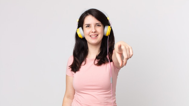 Uma linda mulher apontando para a câmera escolhendo você ouvindo música com fones de ouvido
