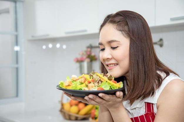 Uma linda mulher asiática cheira molho e pão grelhado da salada de vegetais. idéias sobre culinária saudável e perda de peso.