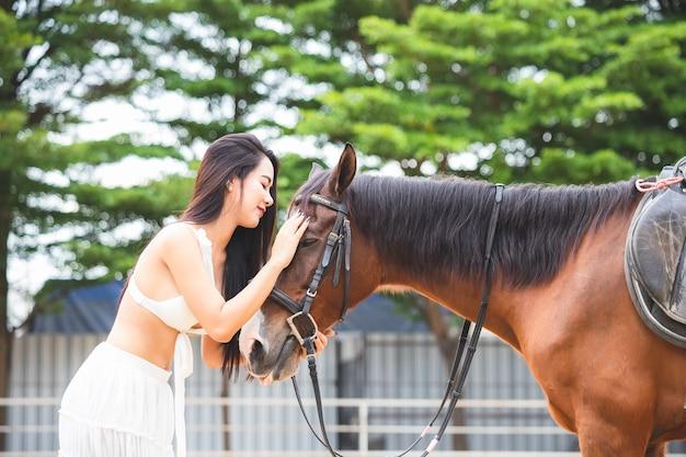 Uma linda mulher asiática de cabelos compridos, tailandesa, ela está usando um vestido branco sexy, ela está esfregando a cabeça de um cavalo com amor
