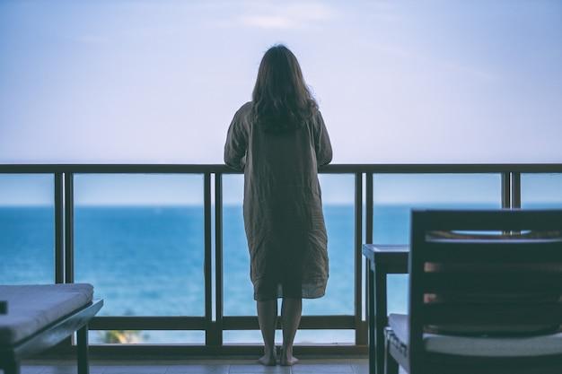 Uma linda mulher asiática em pé apreciando a vista para o mar na varanda