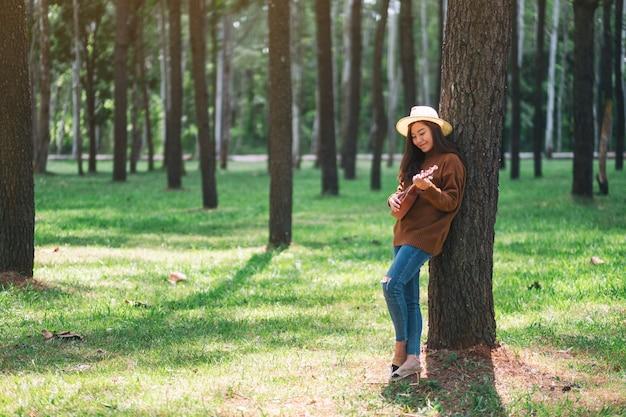 Uma linda mulher asiática em pé e tocando cavaquinho no parque