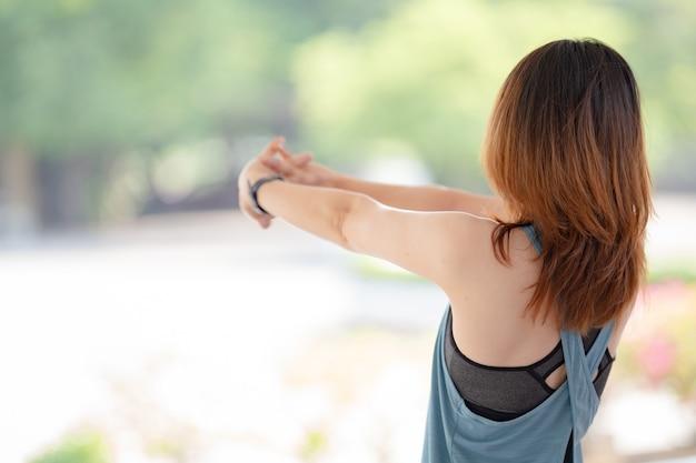 Uma linda mulher asiática em roupas esportivas fazendo alongamento antes dos treinos em casa