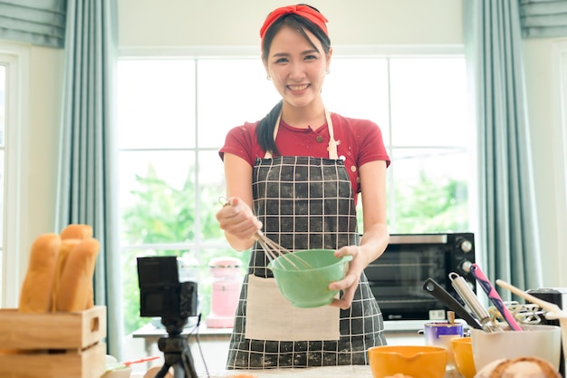 Uma linda mulher asiática está fazendo uma padaria, uma transmissão ao vivo ou gravando um vídeo nas redes sociais em sua casa