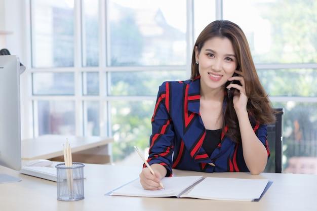 Uma linda mulher asiática está feliz ao telefone falando sobre trabalho e escrevendo um bilhete em papel