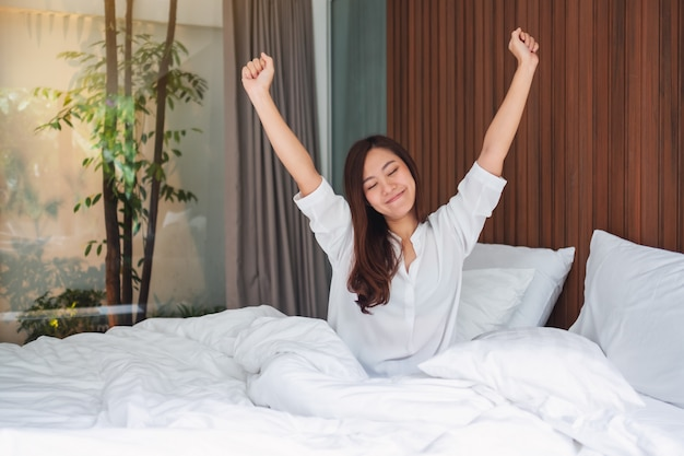 Uma linda mulher asiática faz alongamento depois de acordar de manhã em uma cama branca e aconchegante em casa