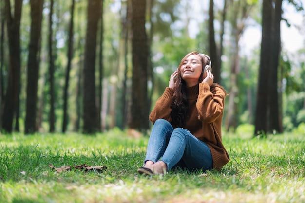 Uma linda mulher asiática gosta de ouvir música com fone de ouvido com o sentimento feliz e relaxado no parque
