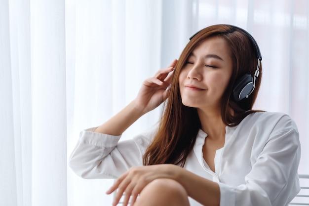 Uma linda mulher asiática gosta de ouvir música com fone de ouvido no quarto, conceitos de felicidade e relaxamento