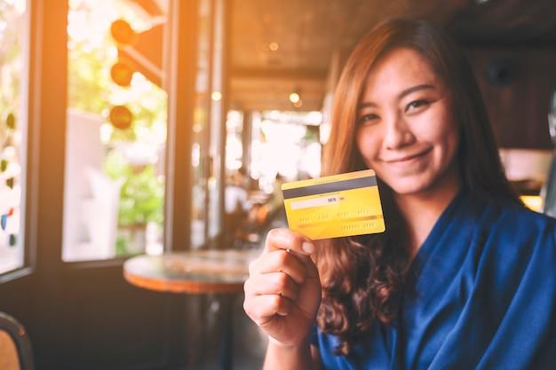 Uma linda mulher asiática segurando um cartão de crédito para fazer compras