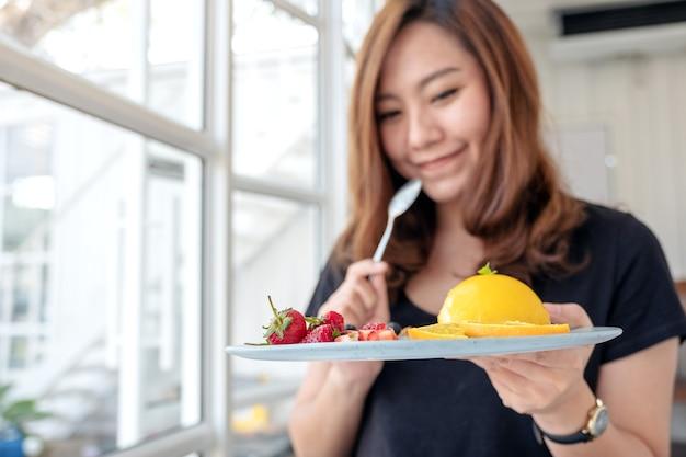 Uma linda mulher asiática segurando um prato de bolo de laranja com uma mistura de frutas e uma colher no café