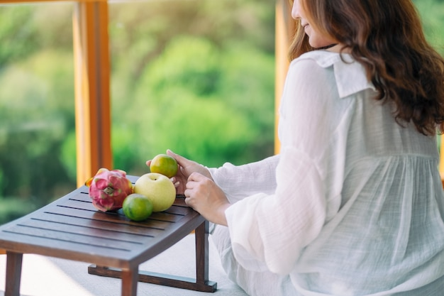 Uma linda mulher asiática segurando uma laranja com pêra e fruta do dragão em uma pequena mesa de madeira