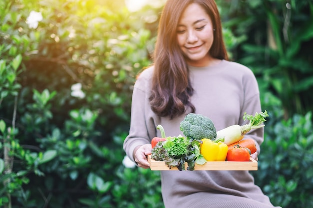 Uma linda mulher asiática segurando uma mistura de vegetais frescos em uma bandeja de madeira