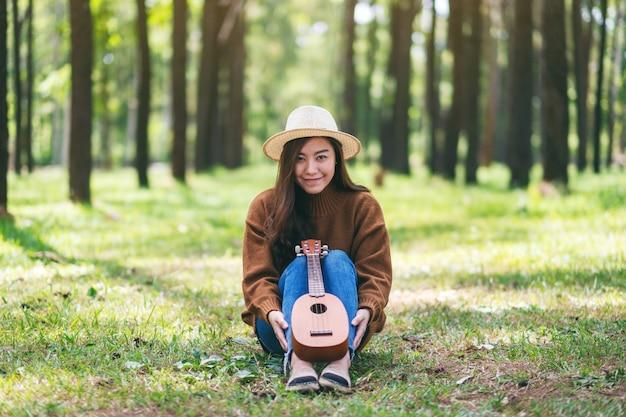 Uma linda mulher asiática sentada com ukulele de madeira no parque